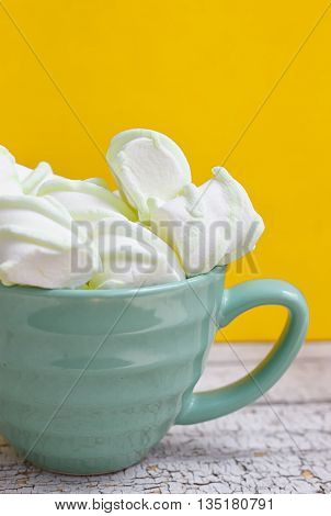 Peppermint large marshmallows in a large green cup on a yellow background