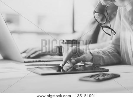 Coworkers team Researching process modern office.Project manager touch tablet screen, holding glasses female hand.Young business crew working startup studio.Using Laptop wood table.Black White.Blurred