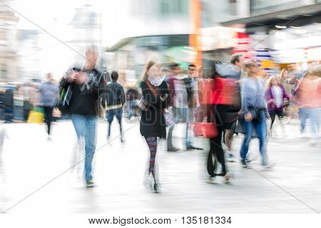 Lots of people, tourists and Londoners walking via Leicester square, Blur background