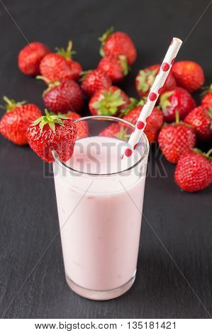Drinking strawberry yogurt in the glass with a straw on a black slate board
