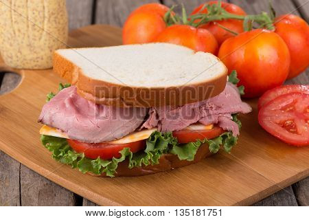 Roast beef sandwich with lettuce tomato and cheese on a cutting board