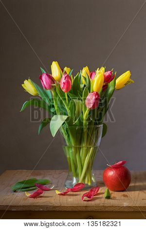 Still life with a bunch of yellow and red tulips and red apple on wooden table