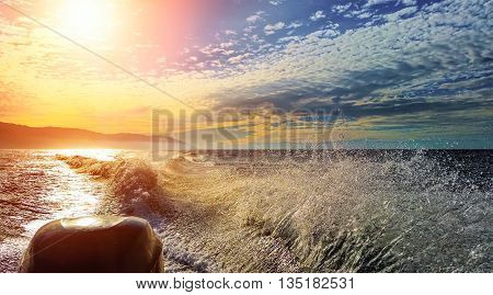 A view from a speedboat ripping water surface and the Sun reflecting in the ocean.