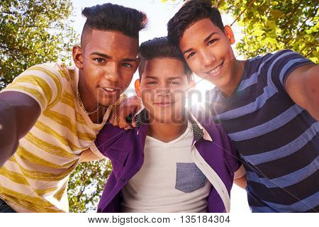 Youth culture young people group of male friends multi-ethnic teens outdoors teenagers together in park. Portrait of happy boys smiling kids looking at camera. Slow motion
