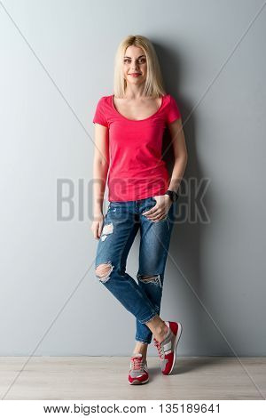 Full length portrait of attractive blond girl standing and leaning on the wall. She is posing with relaxation and smiling. The lady is looking forward with anticipation