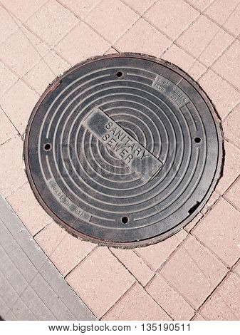 A sewer cap in the street in tile.