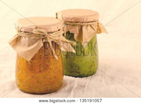 Pumpkin-Orange-Ginger-Poppy seed and Kiwi-Mint homemade jam on white background.