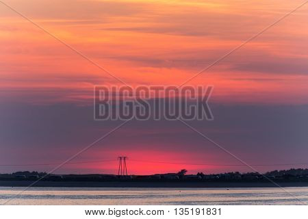 Red sunset over Carnac beach with electric pylons, Brittany, France
