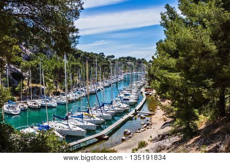 Small fjords in Calanque National Park between Marseille and Cassis.  White sailboats moored in rows near the shore