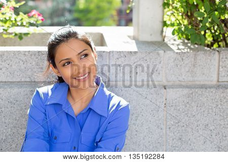 Closeup portrait charming upbeat smiling joyful happy young woman looking upwards daydreaming something nice isolated outdoors gray background. Positive human facial expressions feelings