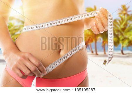 A slim girl measuring her waist, close-up.