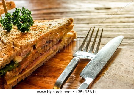 Club sandwich on the wood plate decorate together with fork and knight on the bark wood table background