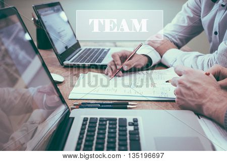 Businessman writing with laptop, pen and paper on table, close up of hands. With TEAM word