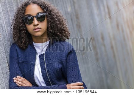 Beautiful mixed race African American girl teenager female young woman outside wearing sunglasses looking sad depressed or thoughtful