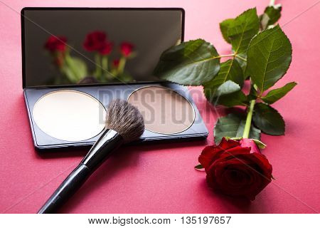 Dry textured correcting powder brush and red rose on dark pink surface. Roses reflecting in the mirror. Makeup product to even out skin tone and complexion. Professional cosmetics.