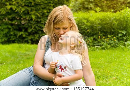 family spends time in nature. mother tenderly embracing daughter