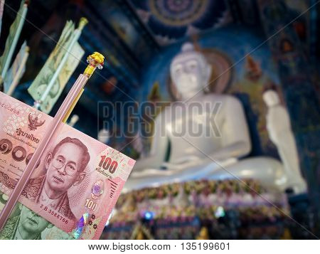 Close-up of Thai banknote for merit in beautiful chapel with blurry white marble Buddha statue background in the temple at north of Thailand. Buddhist culture of Thailand. Low key tone.