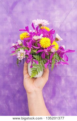 Hand Holding Bouquet Of Chrysanthemum And Orchid Flowers Isolated On Violet Background