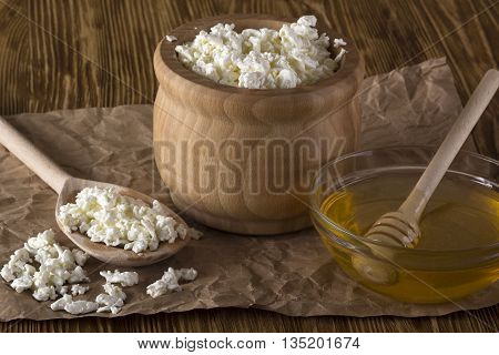 Honey and cottage cheese on the wooden background.
