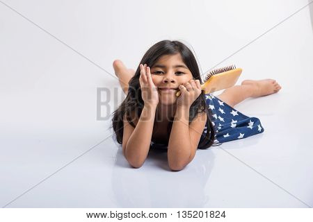 indian small girl combing hair, asian girl with hair brush, small cute indian girl model getting ready with hair brush in hand, small indian girl and hair styling, isolated over white background