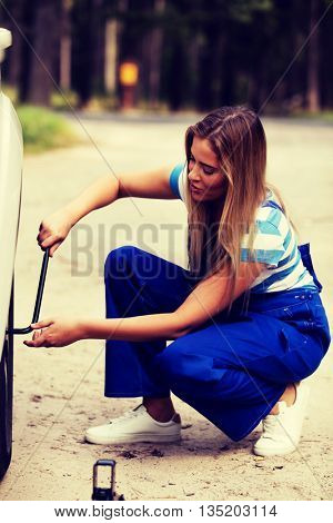 Female mechanic changing tire with wheel wrench
