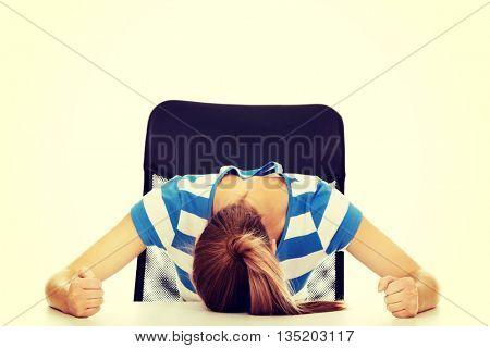 Worried teenage woman sleeping at the desk