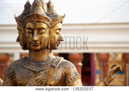 Hindu god Brahma gold shabby old statue in Thailand. Beautiful Indian religion traditional lord sculpture with for faces in a shrine