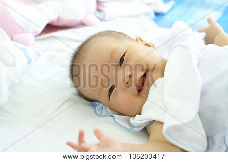Baby girl lying on her bed. Cute baby in white dress is smiling on her bed.