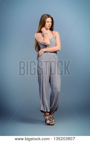 Fashion shot of a beautiful young model with shiny long hair. Healthy hair, haircare.Studio shot over grey background.