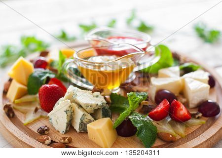 Wine snacks set on wooden cutting board closeup. Fruits and different kinds of cheese with yellow and red sauces on round wooden board. Strawberry, grape, nuts and cheese