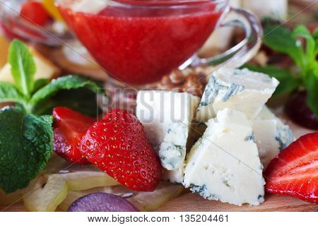 Blue cheese with strawberry and red sauce close-up. Delicious french style snack. Roquefort and fresh strawberry with mint leaves and red sauce