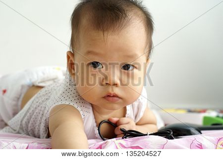 Cute baby lying on the floor. Little infant lying on her bed.