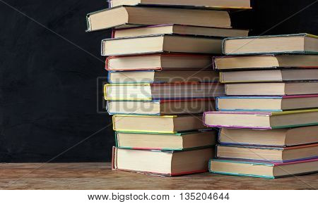 Books in stacks on the table in the background of a school blackboard. Back to school. Left empty space for Your text.