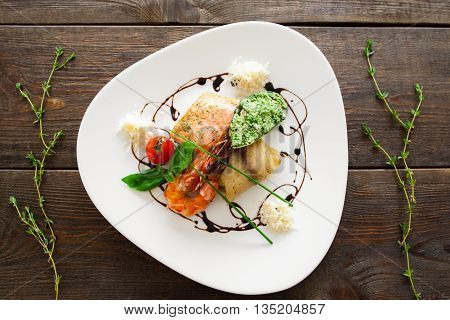 Seafood variety on white plate flat lay. Top view on white triangle plate with different seafood products on wooden background