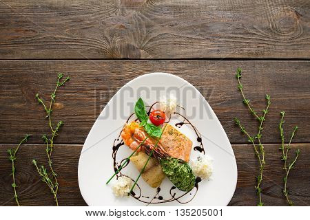 Seafood variety flat lay copyspace. Top view on white triangle plate with stuffed mussel, shrimp, red and white grilled fish with free space for advertisement. Plate with seafood on wood, void