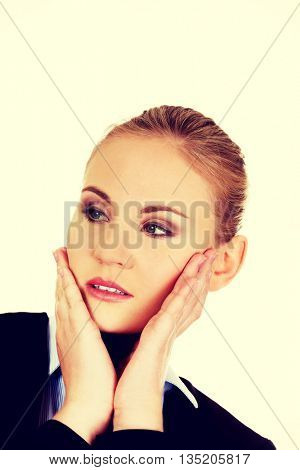 Young worried business woman looking up
