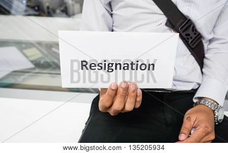 A man is holding a word Resignation with his right hand