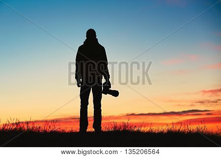 Silhouette of young photographer is enjoying sun. Photographer with mirror camera is ready to take sunrise pictures.