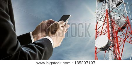 Businessman using mobile phone, with satellite dish telecom network on telecommunication tower on blue sky with sunshine, telecommunication in business and development