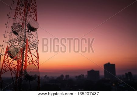 Telecommunications tower and satellite dish telecom network with silhouette of countryside area in sunrise