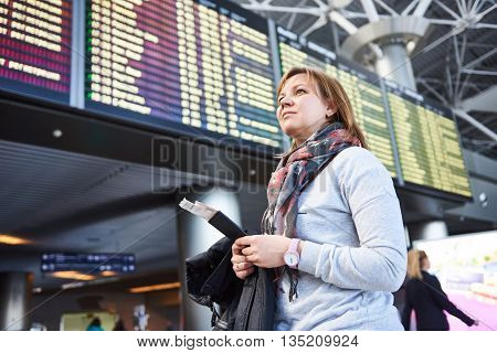 Woman Tourist Standing At Airport On Background Of Departures And Arrivals