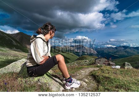 Woman sitting in the mountains observed an alpine hut and the view in the summer