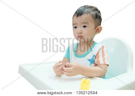 Hungry Asian baby in the highchair. Kid waiting for favorite baby food isolated on white background.
