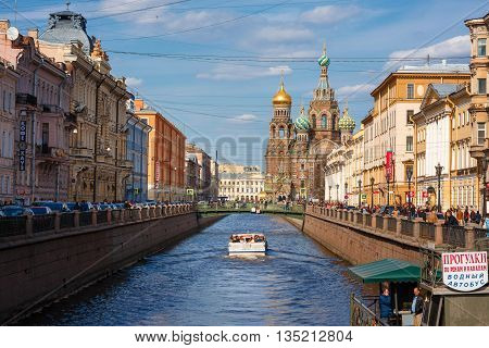ST. PETERSBURG, RUSSIA - April 17, 2016: Church of the Saviour on Spilled Blood, with Tourist in a boat St. Petersburg, Russia