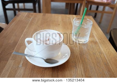 hot fresh coffee in white cup on wooden table with cold glass of water cappuccino coffee mocha coffee espresso coffee latte coffee