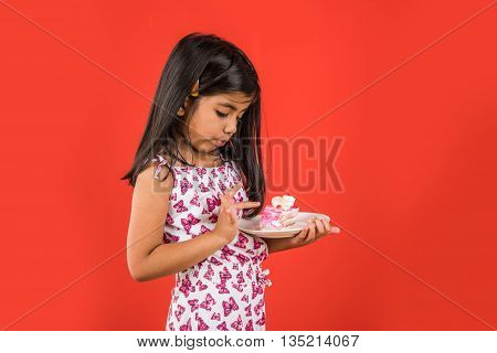 portrait of Indian kid eating cake or pastry, cute little girl eating cake, girl eating piece of chocolate cake or strawberry cake over red background