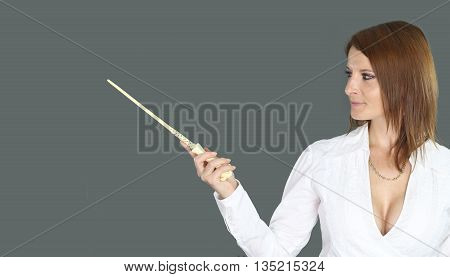 sexy witch holding a magic wand over a gray background
