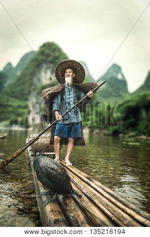 Guilin China - June 17 2014 : Shot of a cormorant fisherman standing on his bamboo raft with the cormorant bird at Li River Guilin China.