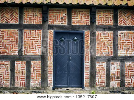 Old half-timbered brick wall house with a blue door - Denmark