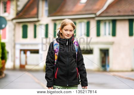 Cute little girl of 8 years old wearing backpack, walking to school